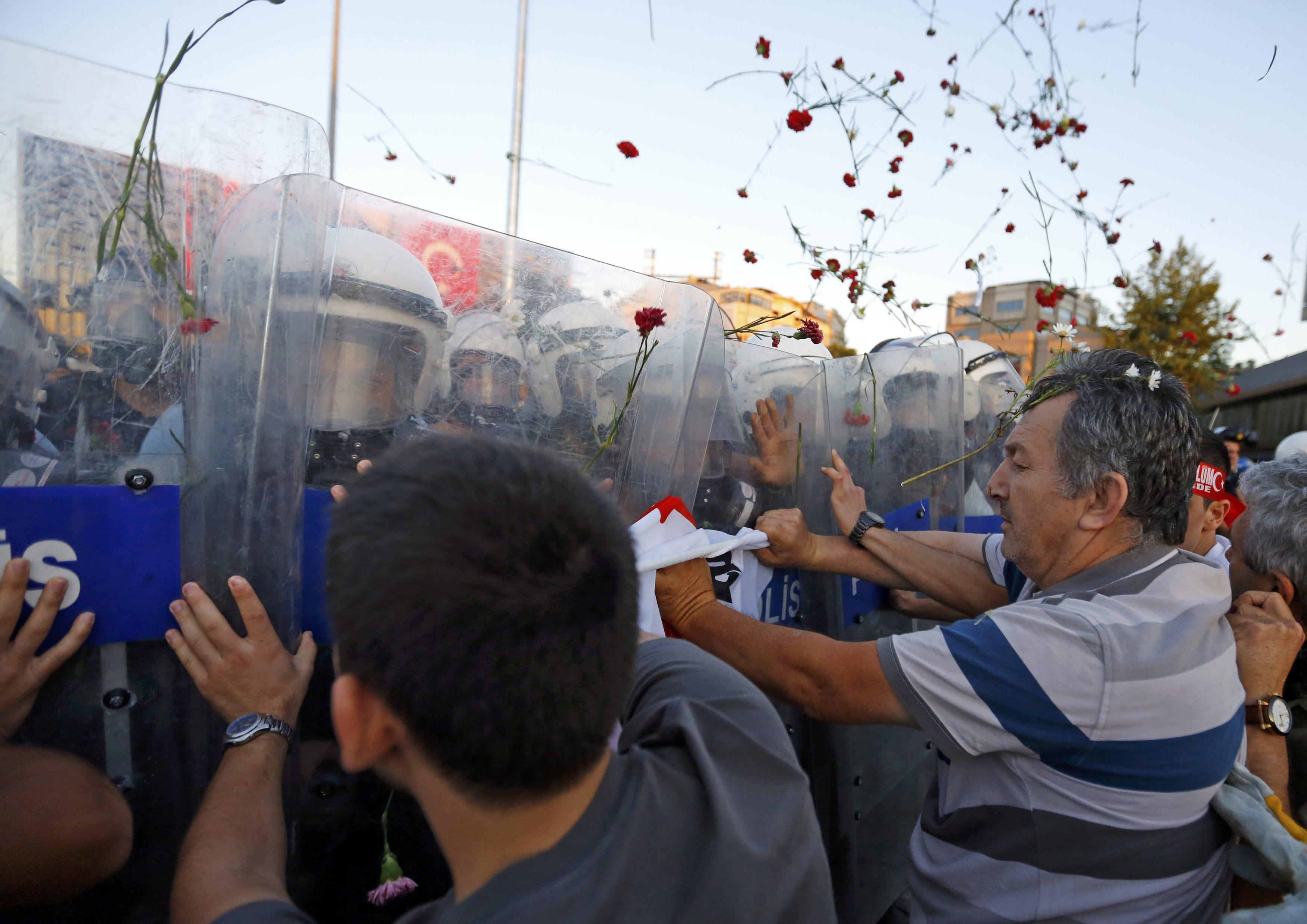 Os cravos que os manifestantes levaram para homenagear as vítimas acabaram por ser atiradas contra os polícias